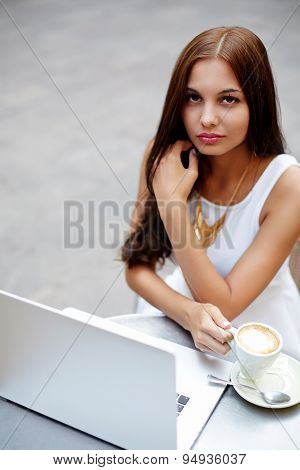 Young businesswoman drink cafe latte while sitting with open laptop computer at coffee shop table