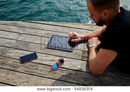 Tourist man using digital tablet while lying on wooden jetty at marina port during his vacation