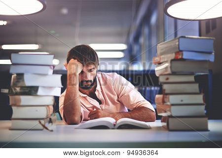 Portrait of caucasian male student sitting at the desk behind stack of book looking exhausted