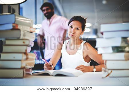Young asian female at hard exam preparation with her classmate standing near bookshelf in study hall