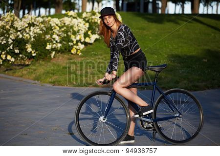 Young pretty woman ready to ride outside on her bicycle promenade at sunny afternoon in summer