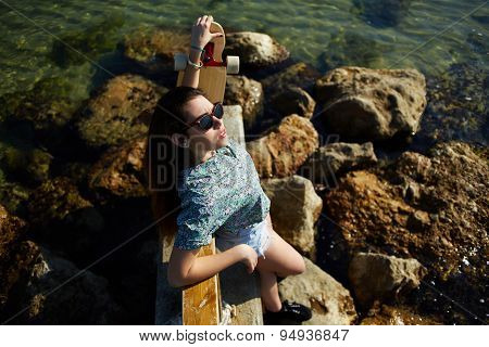 Portrait of woman posing with her skateboard in front of the sea while enjoying summer sunshine