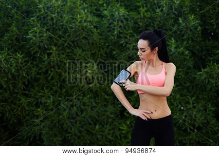 Young sporty woman standing in the park with big copy space for text while getting ready for workout