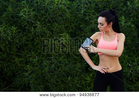 Healthy fit runner setting her personal trainer application or stopwatch on cell phone before a run