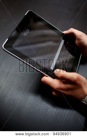 Male hands holding touchpad with a black screen for your text over wooden office table