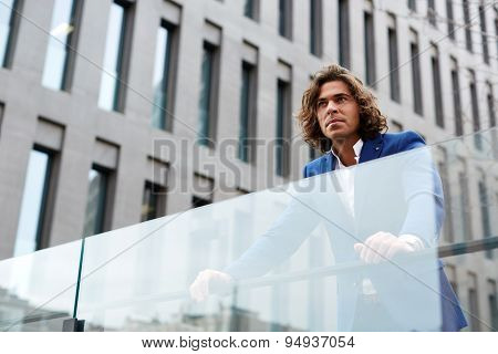 Confident man leaning on glassy fence while standing against big office building in urban setting