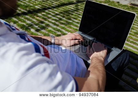 Young tourist working on his computer outdoors in urban setting  while typing on keyboard