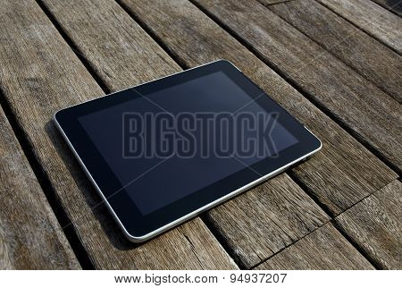 Touchpad wireless device with blank screen for your text message lying on old wooden floor