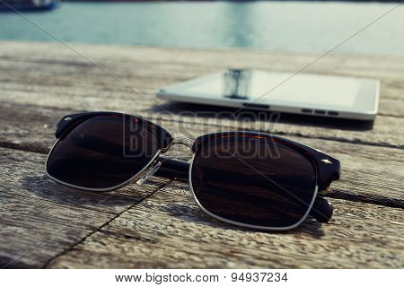 Digital tablet and sunglases lying on wooden jetty with sailing tourist boat on background