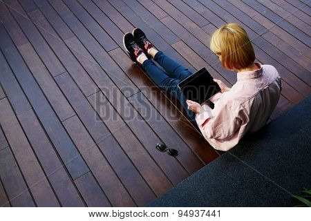 Young female student relaxing in a university recreation hall using touchpad with big copy space