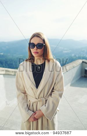 Elegant adult woman dressed in coat standing on beautiful mountains background at sunny day