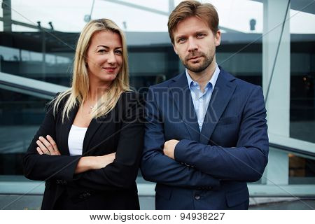 Two young business colleagues standing against office building with brightly smile