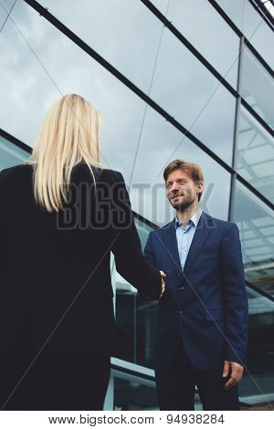 Rear view managing businesswoman shaking hand with smiling employee outside the office