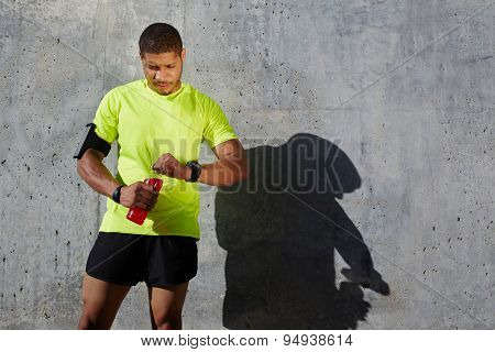 Dark-skinned male athlete in fluorescent t-shirt holding a water bottle looking tired and exhausted