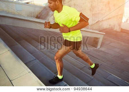 Cropped shot young male dark-skinned athlete running up a flight of stairs with speed