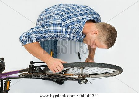 Man Fixing Bicycle Wheel