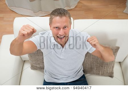 Man Clenching Fist On Sofa