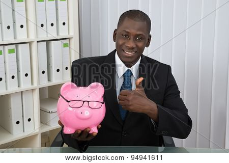 Businessman Showing Thumb Up With Piggybank