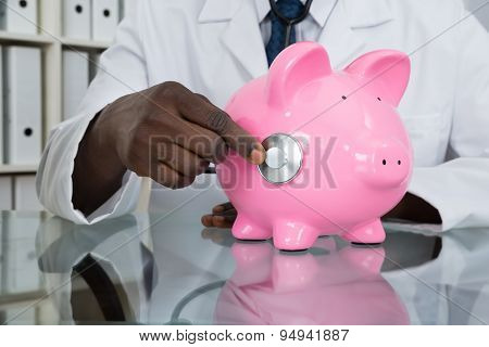Close-up Of Doctor Examining Piggybank With Stethoscope