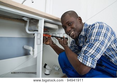 Male Plumber Fixing Pipe Of Sink