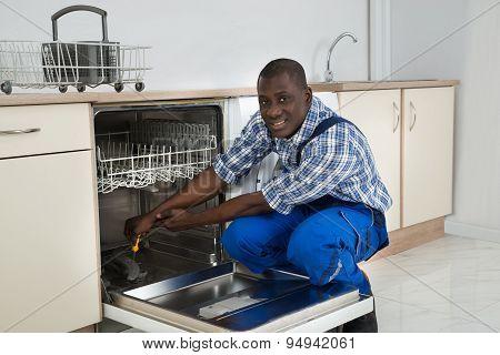 African Repairman Repairing Dishwasher