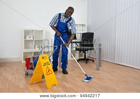 Janitor Cleaning Floor With Wet Floor Sign