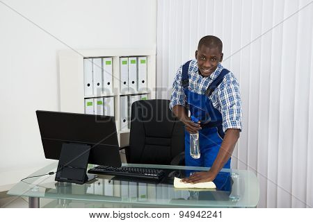 Janitor Cleaning Glass Desk With Cloth In Office