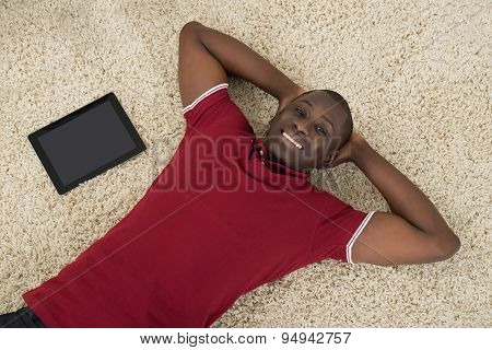 Man With Digital Tablet Lying On Carpet