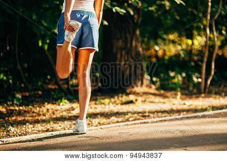 yong sporty woman streching her leg