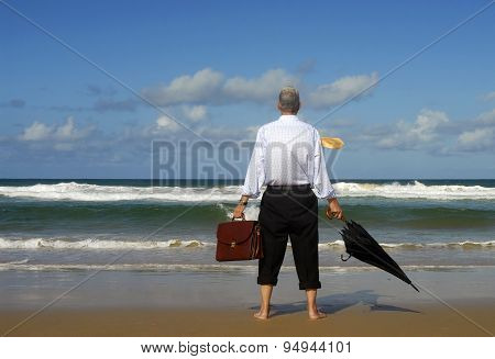 Businessman Gazing Out To Sea Lost In Thought