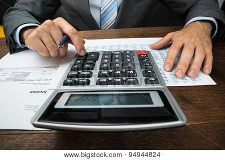 Businessperson Calculating Financial Sheet
