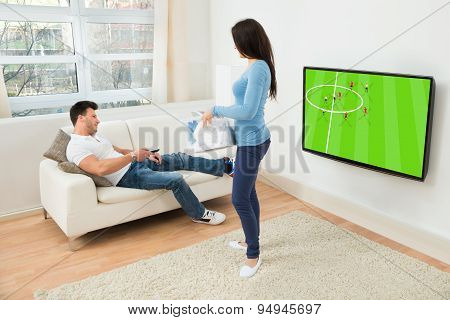 Woman Looking At Man Watching Football Match On Television