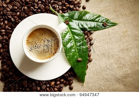 Coffee With Foam Cup With Beans On The Left With Green Leaf On Flax