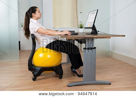 Businesswoman With Fitness Ball And Computer