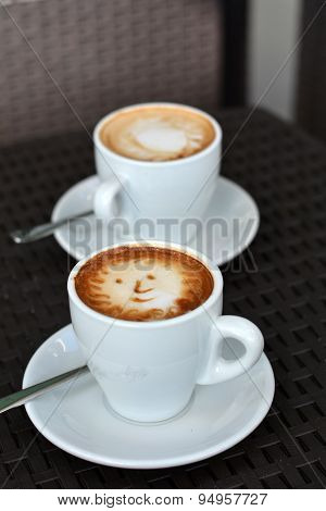 Cup Of Foamy Cappuccino With Smile on A Black Background