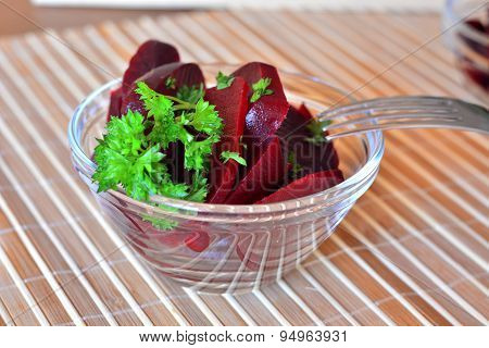 Fresh sliced organic beet root with parsley on a glass bowl