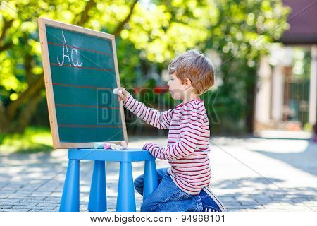 Little Boy At Blackboard Learning To Write