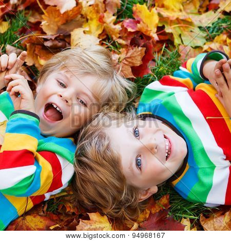 Two Little Kid Boys Laying In Autumn Leaves In Colorful Clothing