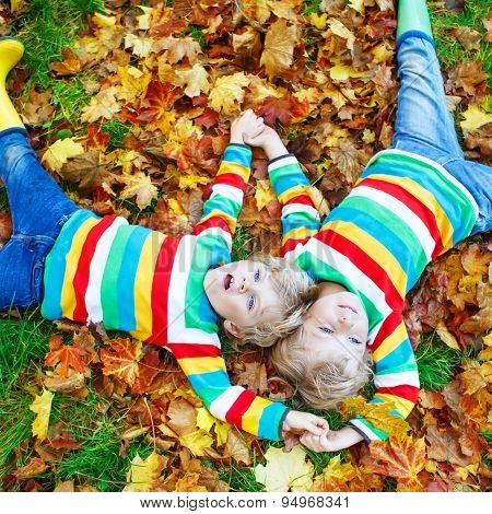 Two Blond Boys Lying In Autumn Leaves In Colorful Clothing. Happy Siblings Having Fun In Autumn Park