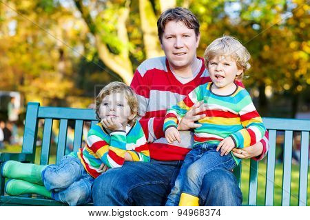 Two Little Kid Boys And Young Father Sitting Together, Autumn, O