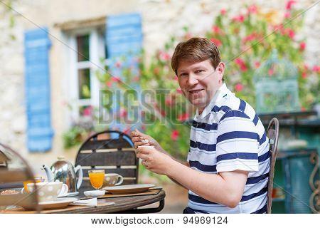 Young Man Having Breakfast Outside In Summer