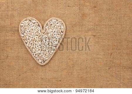 Heart Made From Rope With Sunflower Seeds Lying On Sackcloth