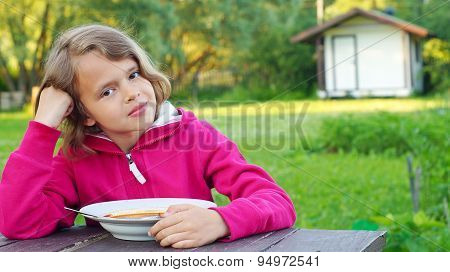 Nice girl eating a soup outdoors