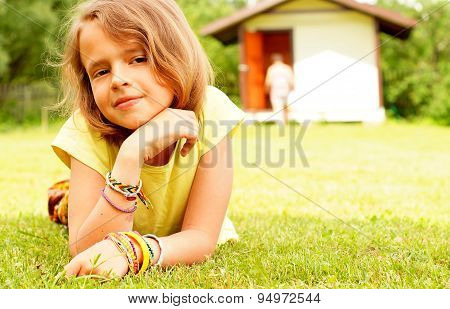 Portrait of girl of ten lying on green grass.
