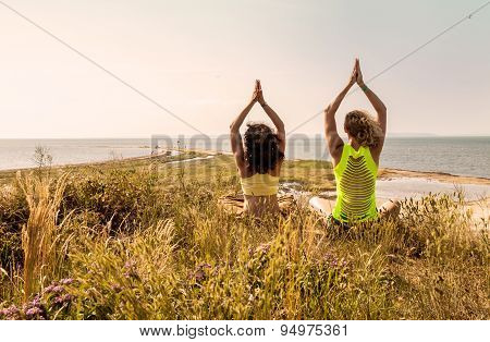 Young women practising yoga on a cliff