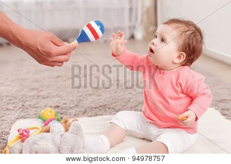 Nice young father holding rattle