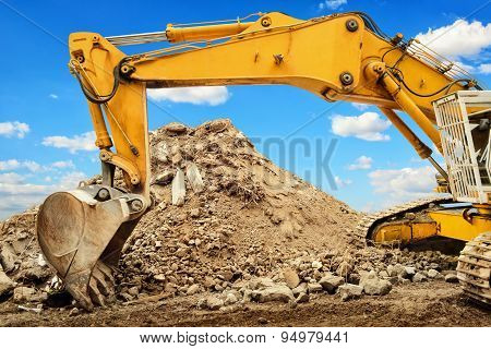Excavator And Heap Of Dirt In Front Of Blue Sky