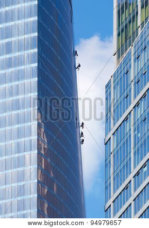 Maintenance Workers Climbing The Outside Wall Of A Skyscraper