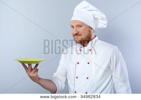Head-cook holding plate and looking at camera