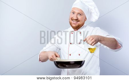 Head-cook holding pan and pouring olive oil in it
